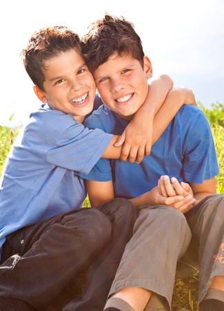 cute brothers sitting in a meadow photo