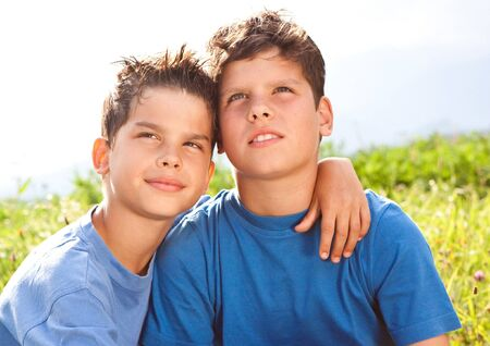 future twin: cute brothers sitting in a meadow