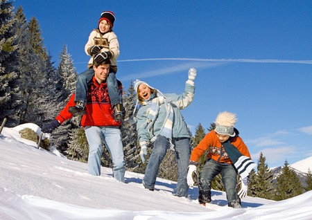 snowy mountain: young family having fun in winter landscape
