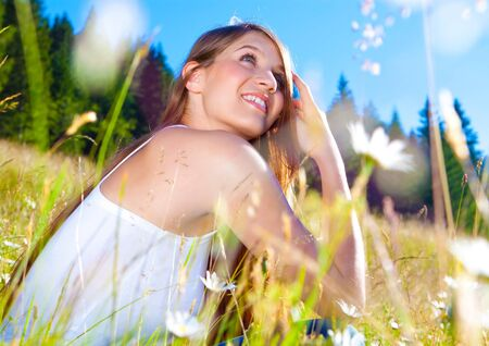 emotional freedom: young pretty girl sitting in a marguerite-meadow