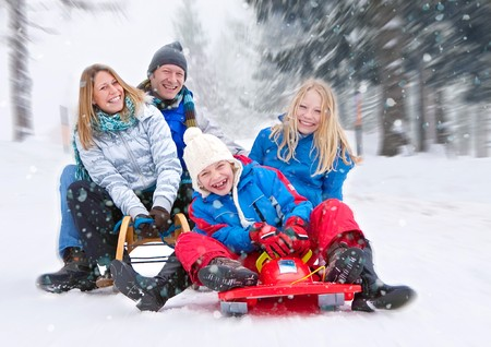 sled: young funny family is sledging in winter-landscape Stock Photo