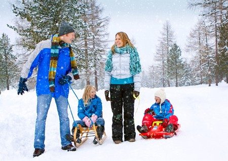 snow woman: young funny family is sledging in winter-landscape Stock Photo