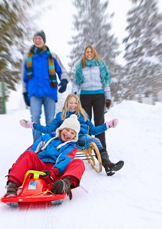 active girl: young funny family is sledging in winter-landscape Stock Photo