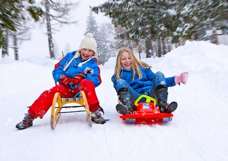toboggan: sisters are sledging in winter Stock Photo