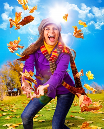 fall fun: young happy woman with foliage in autumn