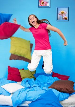 jaunty: adolescentes-mujer joven est� haciendo una lucha de almohadas  Foto de archivo