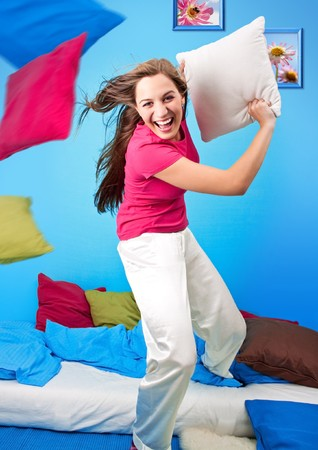 women fight: young teenage-woman is making a pillow-fight Stock Photo