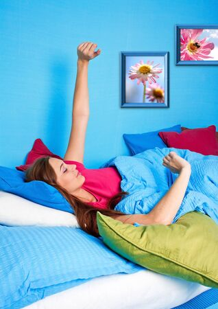 young girl yawing in bed before standing up photo