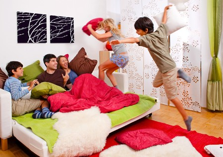 a young family is making a pillow-fight in their bedroom photo