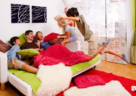 a young family is making a pillow-fight in their bedroom Standard-Bild