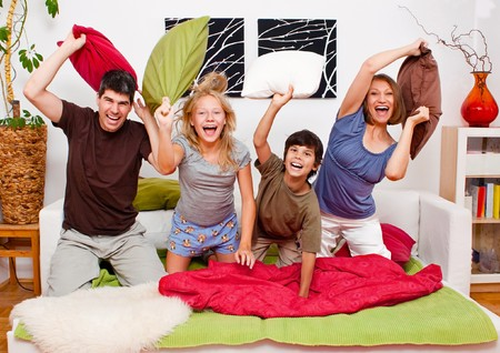 throw cushion: a young family is making a pillow-fight in their bedroom Stock Photo