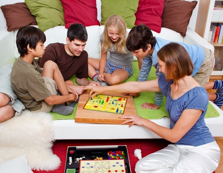 a young family is playing board-games in their bed Stock Photo - 7596084