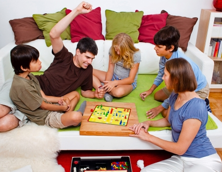 a young family is playing board-games in their bed photo