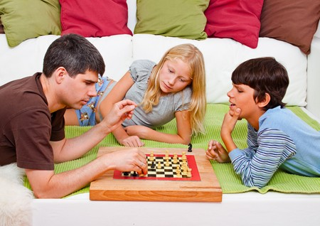 a young father is playing chess with his children photo