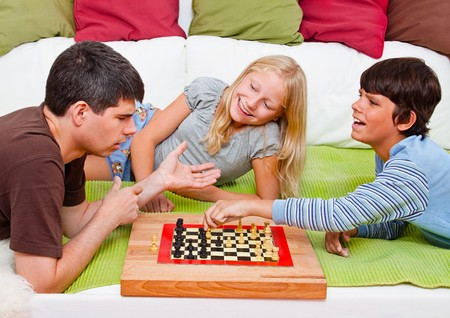 boardgames: a young father is playing chess with his children