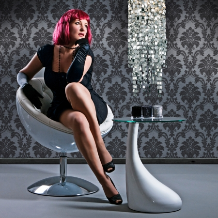 elegant stunning woman with read hair sitting on a modern chair Stock Photo - 14031603