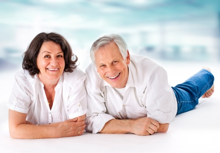 sitting on floor: attracitve senior couple having fun together