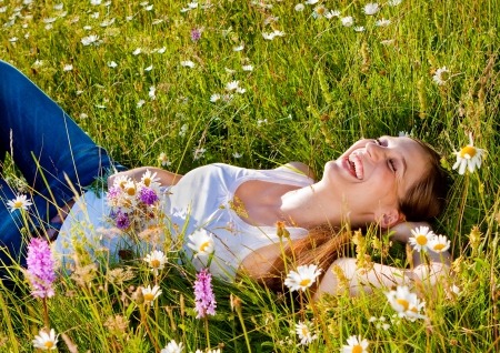 at ease: beautiful girl lying in a summer-flower-meadow