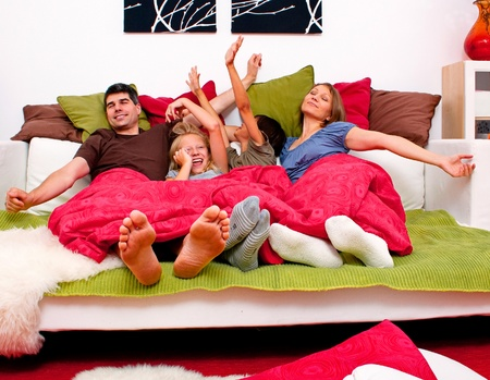 family couch: happy young familiy having fun in their bed