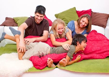 jaunty: familiy joven feliz que se divierte en la cama Foto de archivo