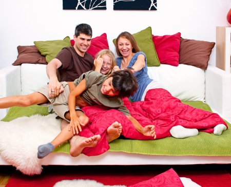 happy young familiy having fun in their bed