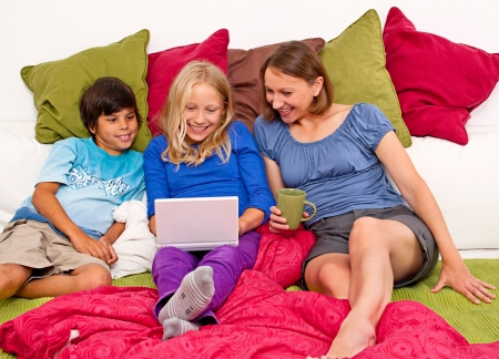 comfort room: mother sitting in bed with her children and learning with a computer
