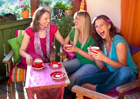 afternoon tea: girlfriends drinking coffee and talking on a comfortable terrace