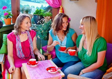 afternoon: amigas tomando caf� y hablando en una c�moda terraza