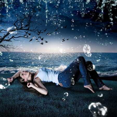 beautiful girl lying in the rain on a meadow in the evening photo
