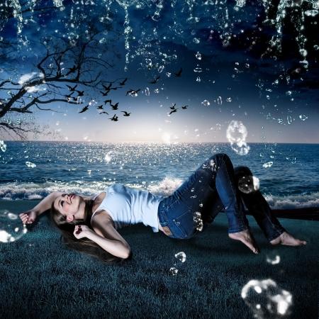 noche estrellada: hermosa niña acostada en la lluvia en un prado en la noche