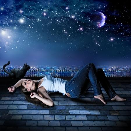 sterrenhemel: een meisje en een kat liggen op een dak onder de sterrenhemel Stockfoto