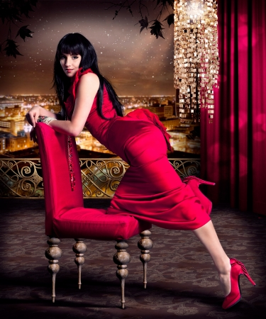 traje de gala: hermosa mujer con vestido de noche rojo en una terraza con horizonte de la ciudad detr�s de