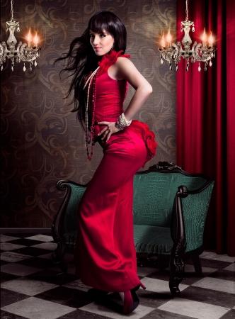 velvet dress: beautiful woman in eveningdress standing in front of an victorian chair
