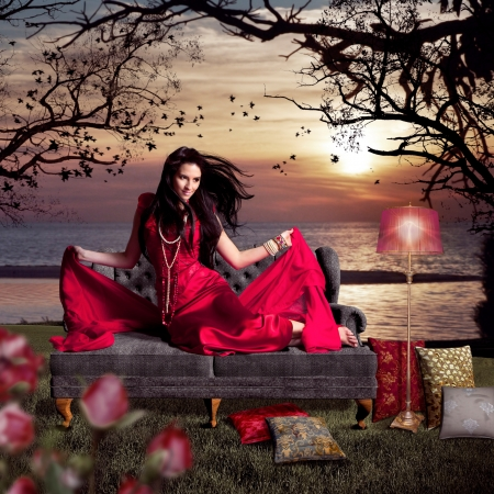 nobility: beautiful woman sitting on an old sofa beside a lake Stock Photo
