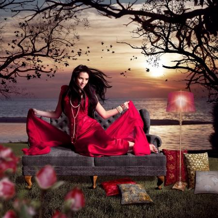 beautiful woman sitting on an old sofa beside a lake Stock Photo