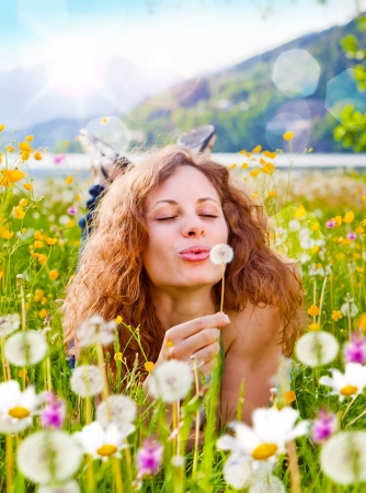 puffing: sweet girl in a meadow full of dandelions Stock Photo