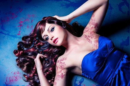 dramatically: girl with beautiful colored curly hair lying on a painted floor like a doll Stock Photo