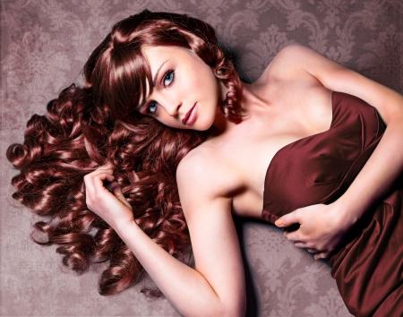 pelo rojo: chica imponente con el pelo rizado, que pone en una hermosa alfombra de época