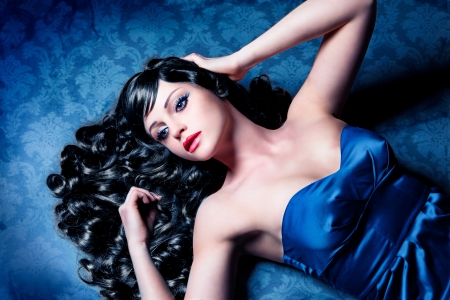 stunning lady with black glossy hair lying on the floor photo