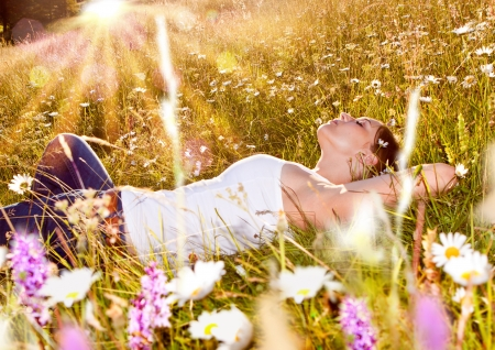 girl relaxing in meadow full of flowers in the sunset