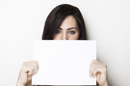 Beautiful girl holding a white blank paper in her hands photo