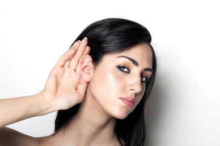 Beautiful girl putting her hand near the ear