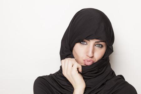 burqa: Beautiful transgressive girl with kissing lips wearing a burqa Stock Photo