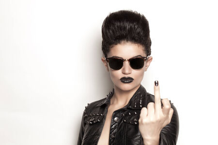 middle finger: Beautiful rocker girl wearing a leather jacket and sunglasses Stock Photo