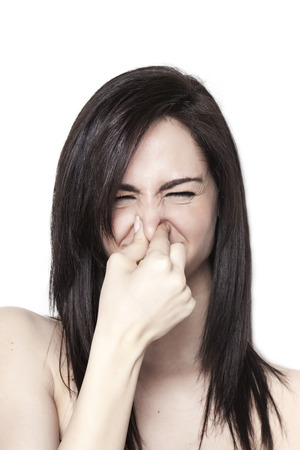 disgusted: Beautiful upset girl smelling stench Stock Photo
