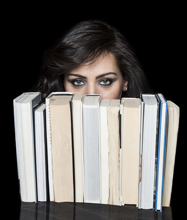Beautiful girl with deep look hiding behind a book shelf photo