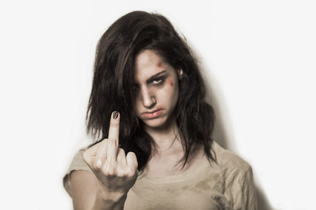 Angry beaten up girl with wounds on the face showing middle finger