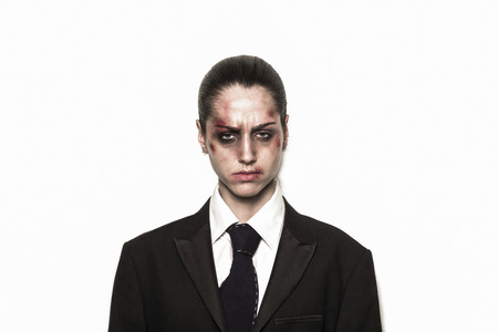beaten up: Sad beaten up girl with wounds on the face wearing a business suit and looking at the camera Stock Photo