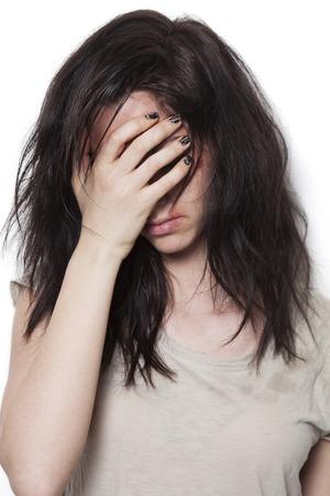 Sad geslagen meisje met wonden op het gezicht die haar gezicht met de hand