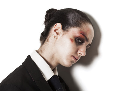 Sad beaten up girl with wounds on the face wearing a business suit and looking at the camera photo